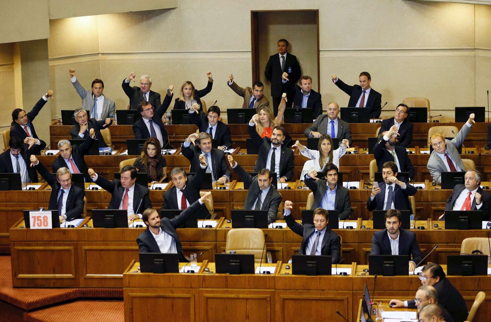 Diputados de la derecha hacen gestos en contra de la ley del aborto. Fotografía de Rodrigo Garrido. Reuters.